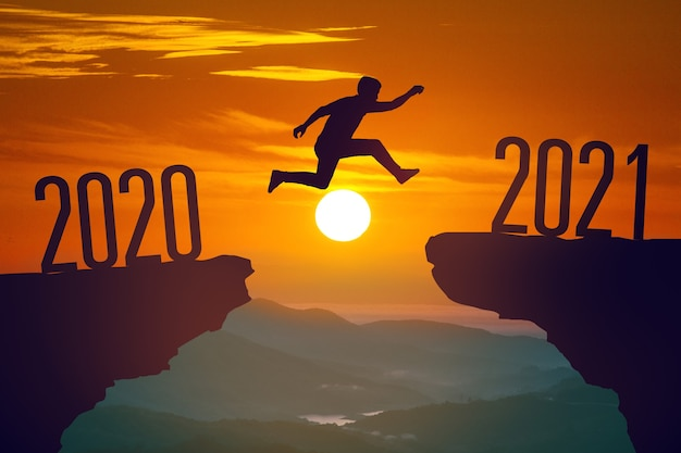 Sylwetka młodego mężczyzny skaczącego między 2020 a 2021 rokiem z zachodem słońca