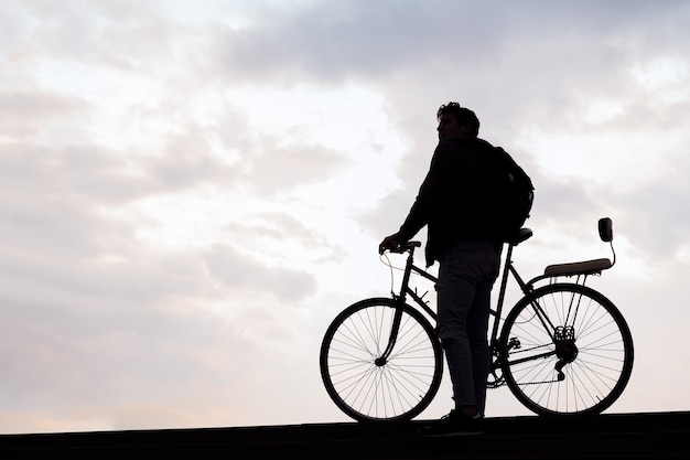 Sylwetka młodego mężczyzny z plecakiem trzymającego koncepcję roweru zrównoważonego stylu życia