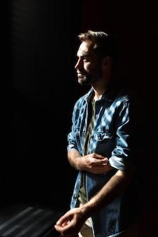 Sylwetka młodego zamyślonego mężczyzny stojącego w ciemnym pokoju przed światłem słonecznym z okna na rolety cieniowe