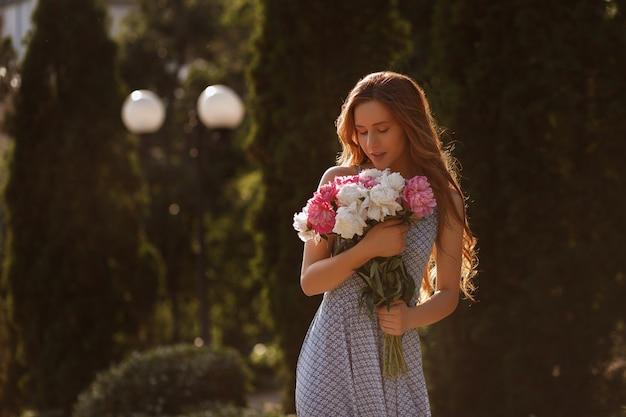 Sylwetka młodej dziewczyny o zachodzie słońca. w jej rękach bukiet letnich kwiatów