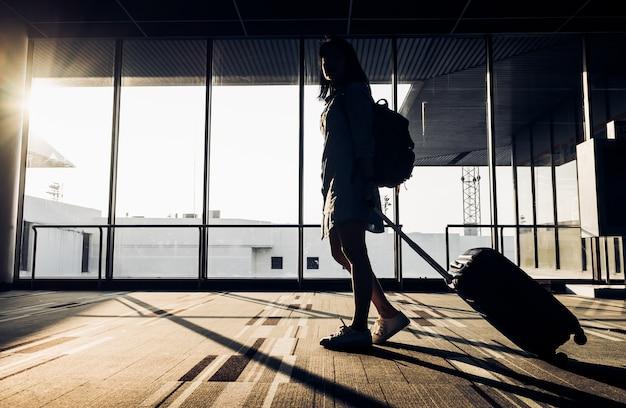 Sylwetka młodej dziewczyny odprowadzenie z bagażu odprowadzeniem przy lotniskiem