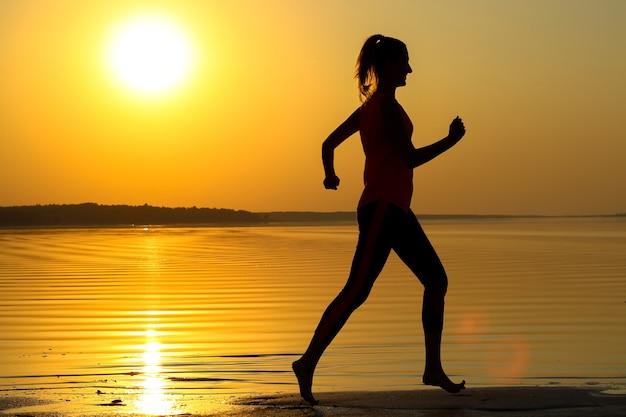 Sylwetka młodej dziewczyny piękne biegnie wzdłuż brzegu morza na pomarańczowym tle zachodu słońca.