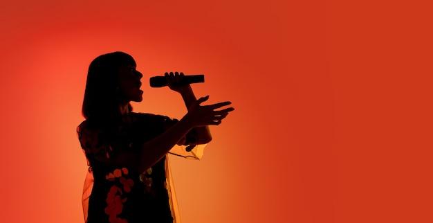 Sylwetka młodej kaukaskiej piosenkarki odizolowanej na pomarańczowym tle studio gradientu w neonowym