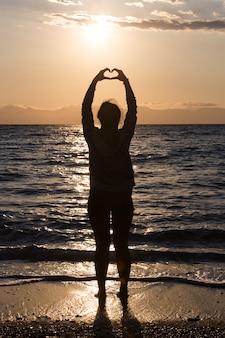 Sylwetka młodej kobiety co serce w kształcie dłoni o wschodzie słońca na plaży.