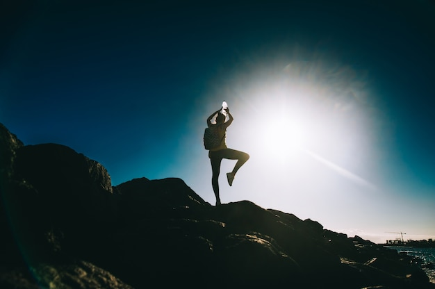 Sylwetka młodej kobiety ćwiczy joga na skalistym brzeg