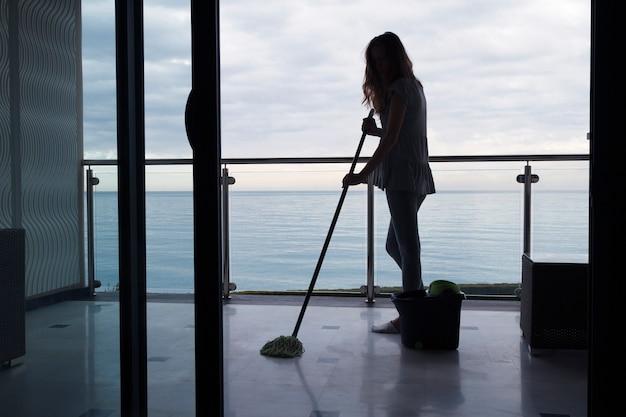 Sylwetka młodej kobiety myjącej mop z marmurową posadzką na balkonie na zewnątrz