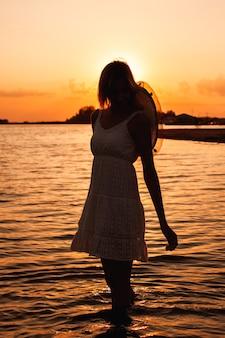 Sylwetka młodej kobiety na tle zachodu słońca zdjęcie pięknej szczupłej kobiety w letniej...