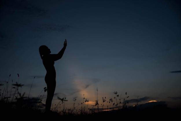 Sylwetka młodej kobiety sam na sam z bogiem o zachodzie słońca