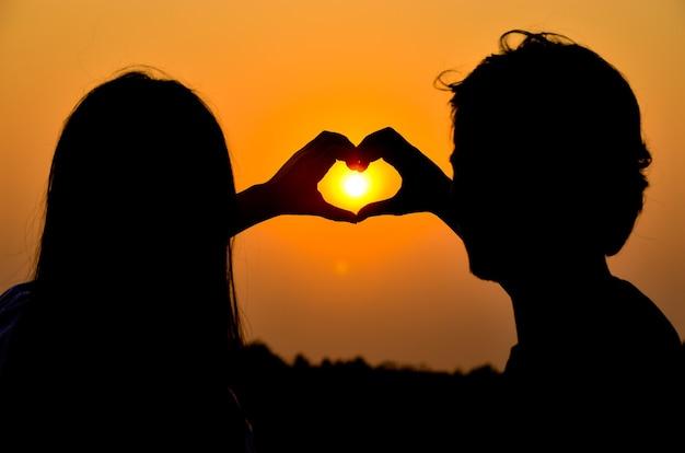 Sylwetka młodej pary układa rękami kształt serca podczas romantycznych wakacji