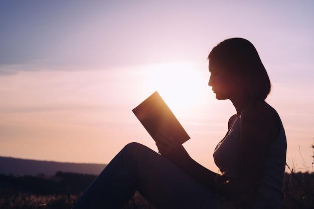 Sylwetka młodej pięknej kobiety o świcie siedzi na ziemi i uważnie wpatrując się w otwartą książkę