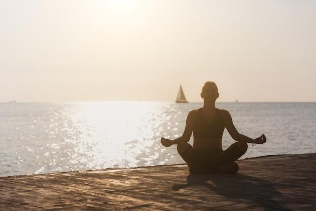 Sylwetka młodej wysportowanej dziewczyny uprawiającej jogę o wschodzie słońca na plaży z żaglówką