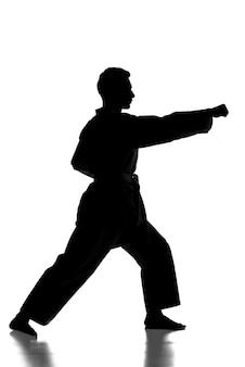 Sylwetka młody człowiek ćwiczy sztuki walki.