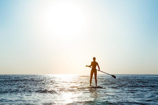 Sylwetka młody piękny kobieta surfing w morzu przy wschodem słońca.