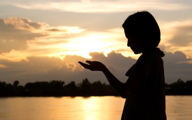 Sylwetka modlenie nad pięknym zmierzchu tłem kobieta.