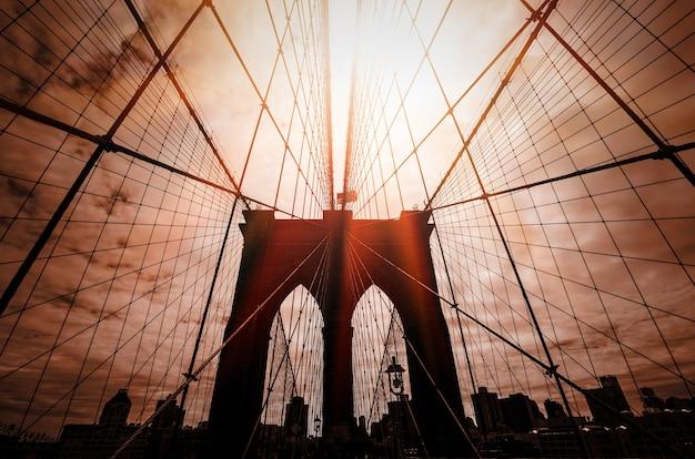 Sylwetka mostu brooklyn z dramatycznym czerwonym niebem i promieniami słońca. nowy jork. usa.