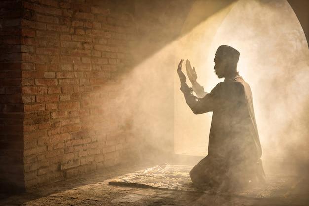 Sylwetka muzułmanina modlącego się w starym meczecie w prowincji phra nakhon si ayutthaya, azja muslim