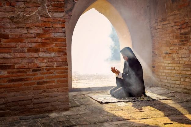 Sylwetka muzułmańskiej dziewczyny modlącej się i życzącej allahowi w starym meczecie, prowincja phra nakhon si ayutthaya, tajlandia