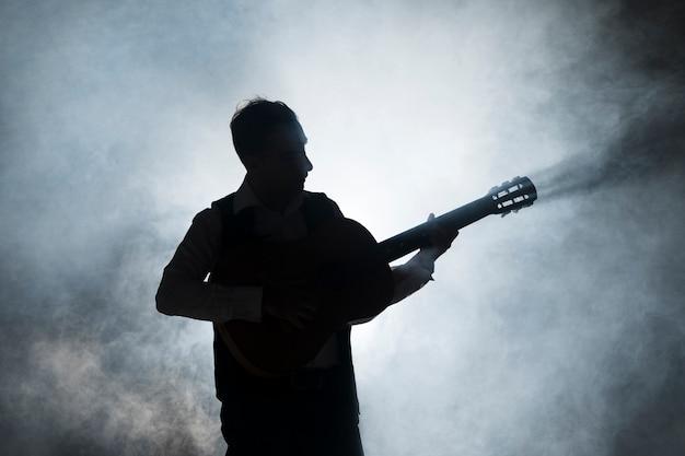 Sylwetka muzyka na scenie, grając na gitarze