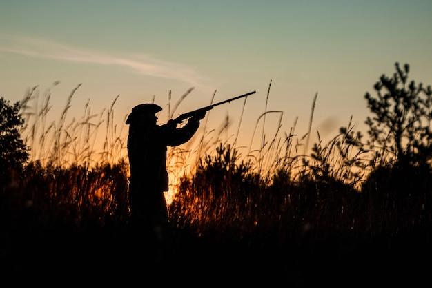 Sylwetka myśliwego w kowbojskim kapeluszu z bronią w ręku na piękny zachód słońca