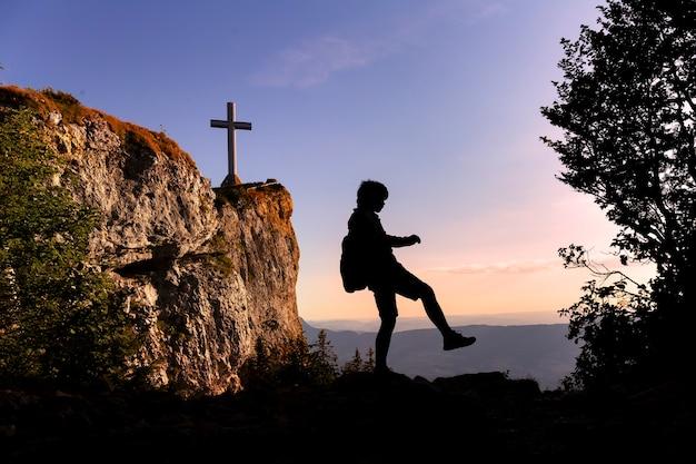 Sylwetka nastolatka chodzącego na szczycie góry o zachodzie słońca podróżujących samotnie