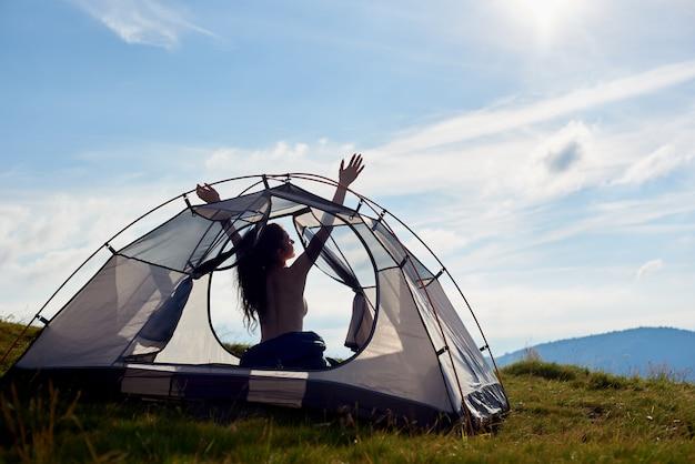 Sylwetka obozowicza naga kobieta siedzi w namiocie