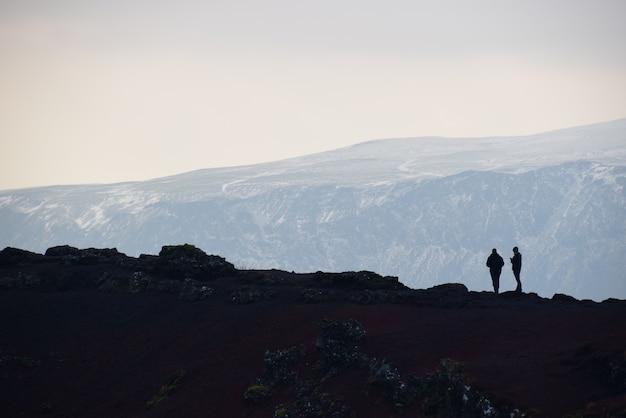 Sylwetka obrazek 2 podróżnika chodzić na krawędzi krateru jeziora przy iceland.