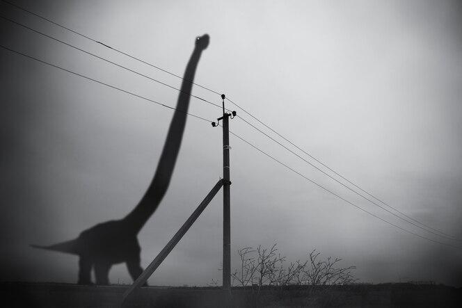 Sylwetka ogromnego brontozaura w ciemnej mgle i słupie z przewodami elektrycznymi, ponury fantastyczny kolaż