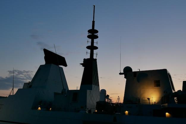 Sylwetka okrętu wojennego o zachodzie słońca