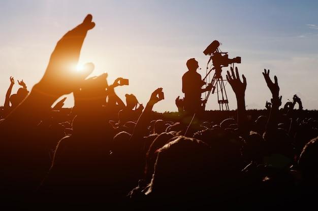 Sylwetka operatora kamerzysty kręcącego letni koncert rockowy na żywo, fani wokół uniesionych rąk