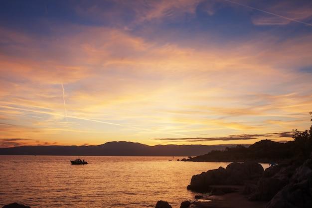 Sylwetka osamotniona łódź w zmierzchu z dramatycznym niebem. zachód słońca na pełnym morzu ze statku rybackiego na horyzoncie.