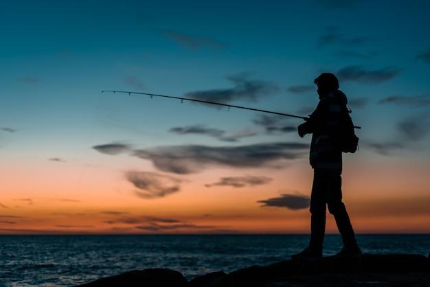 Sylwetka osoby łowiącej ryby w morzu