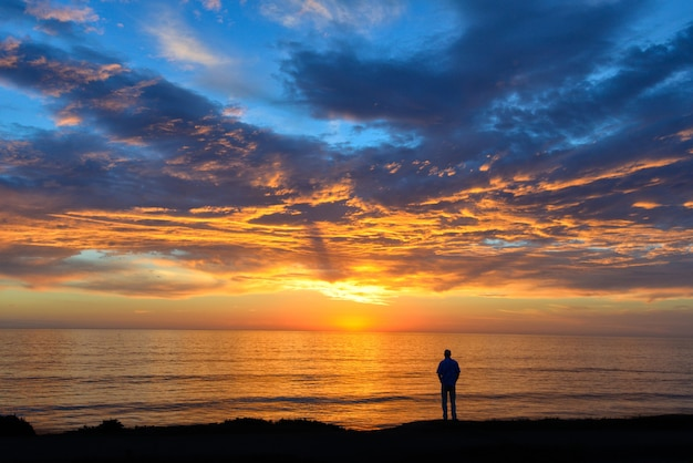 Sylwetka osoby stojącej na plaży pod zachmurzonym niebem podczas zapierającego dech w piersiach zachodu słońca