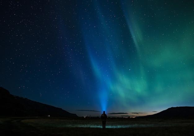 Sylwetka osoby stojącej pod nocnym niebem aurora