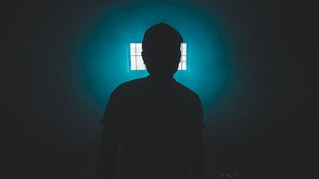 Sylwetka osoby stojącej w ciemnym pokoju