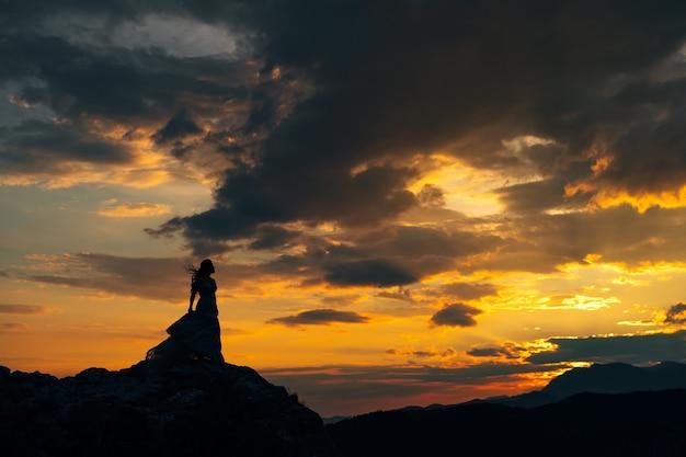 Sylwetka panny młodej stojącej na skałach w górach o zachodzie słońca