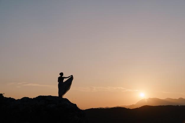 Sylwetka panny młodej stojącej na szczycie góry o zachodzie słońca