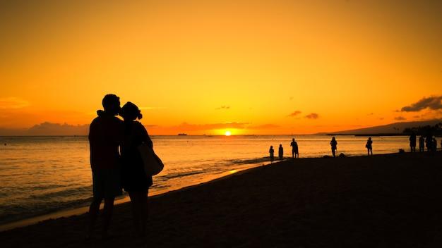 Sylwetka para zakochanych całuje o zachodzie słońca