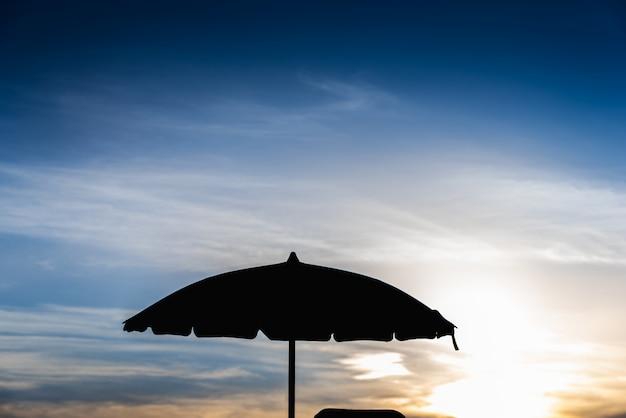 Sylwetka parasol plażowy przed podświetleniem w gorący letni dzień.