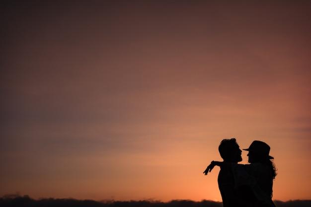 Sylwetka pary, która patrzy na siebie i przytula pod światło o zachodzie słońca.