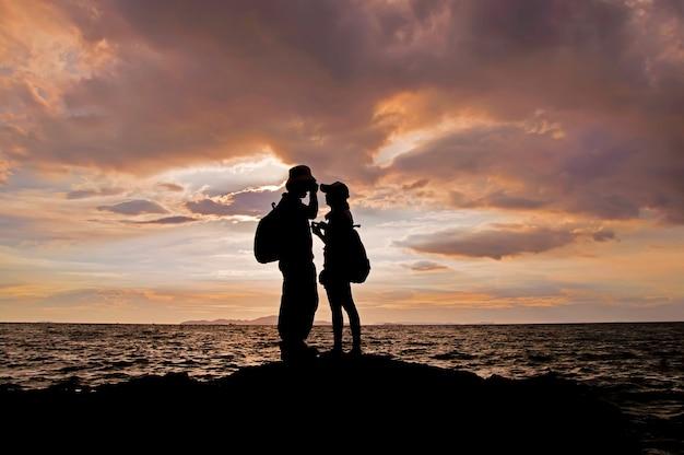 Sylwetka pary mienia ręki na plaży przy zmierzchem