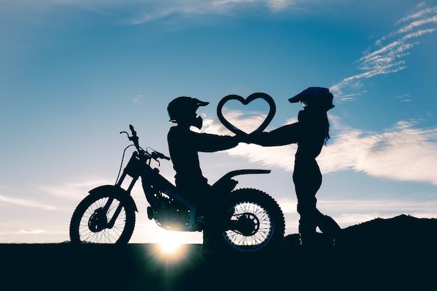 Sylwetka pary pozycja i kierowy kształt w handwith motocykl w zmierzchu