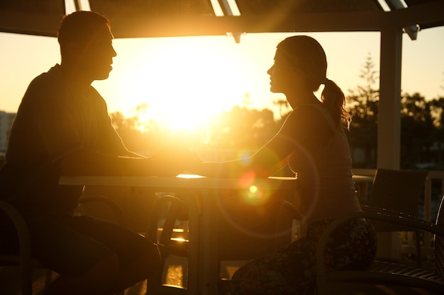 Sylwetka pary siedzącej przy stole o zachodzie słońca