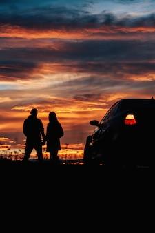 Sylwetka pary stojącej przy samochodzie na tle pięknego nieba o zachodzie lub świcie.