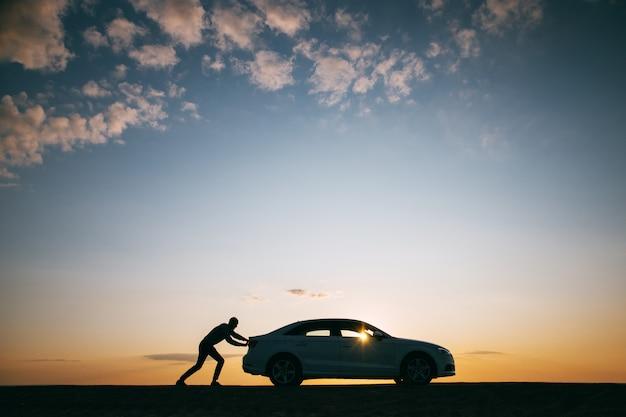 Sylwetka pcha jego samochód po awarii przy zmierzchem mężczyzna kierowca