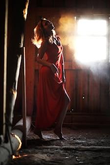 Sylwetka pięknej dziewczyny w czerwonej sukience na tle okna w starym domu