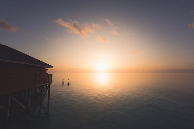 Sylwetka piękny tropikalny maldives hotel w kurorcie i wyspa z plażą i morzem