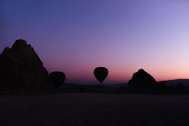 Sylwetka pięknych balonów na ogrzane powietrze o wschodzie słońca w kapadocji