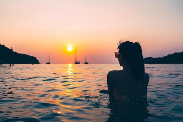 Sylwetka podróżnika azjatyckie kobiety z bikini relaks na plaży o zachodzie słońca w koh kood, tajlandia