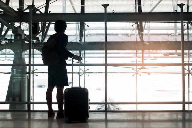Sylwetka podróżnika z bagażu walizki i plecaka wygląd przez okno na lotnisku