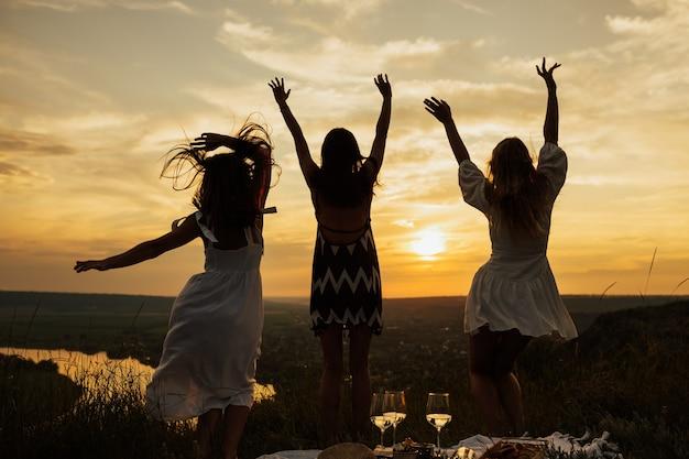 Sylwetka podskakujących szczęśliwych dziewcząt z kręconymi włosami w letniej sukience z idealnym zachodem słońca.